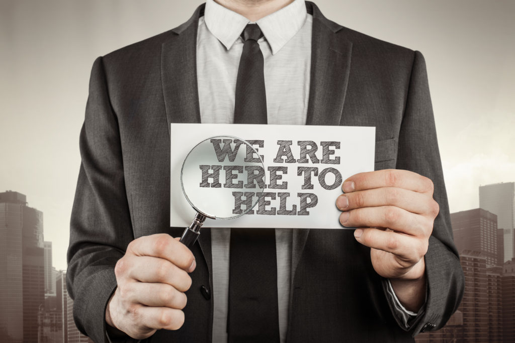 Businessman in a suit is holding a magnifying glass and paper which reads we are here to help.